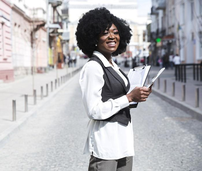smiling-young-african-businesswoman-standing-city-road-holding-clipboard-looking-away